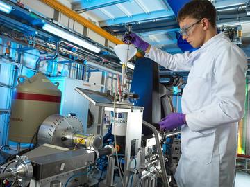Researcher loading sample onto beamline